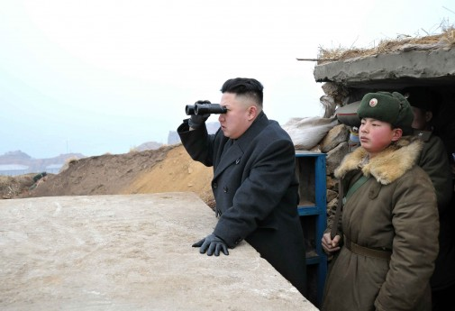 North Korean leader Kim Jong-Un uses a pair of binoculars to look towards the South