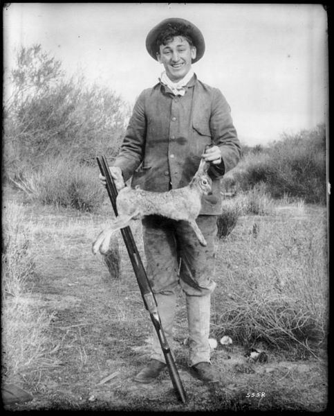 Portrait_of_a_hunter_holding_a_dead_jackrabbit_by_the_ears_and_tail,_ca.1900_(CHS-5552)