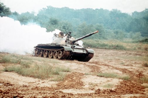 Right front view of a Soviet-built T-62 main battle tank laying a smoke screen.